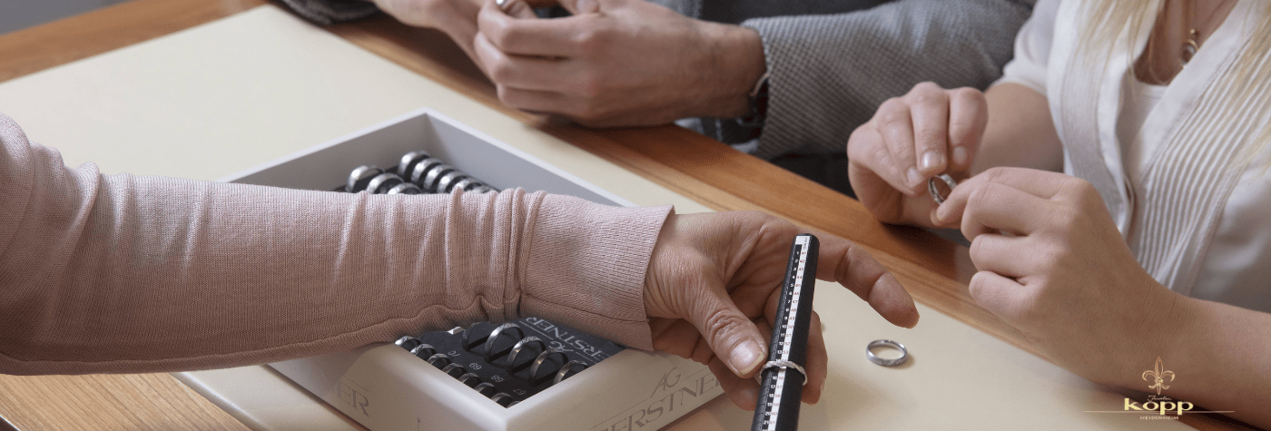 Hände von Kunden und Mitarbeiterin des Juwelier Kopp Heidenheim beim Ringgröße messen