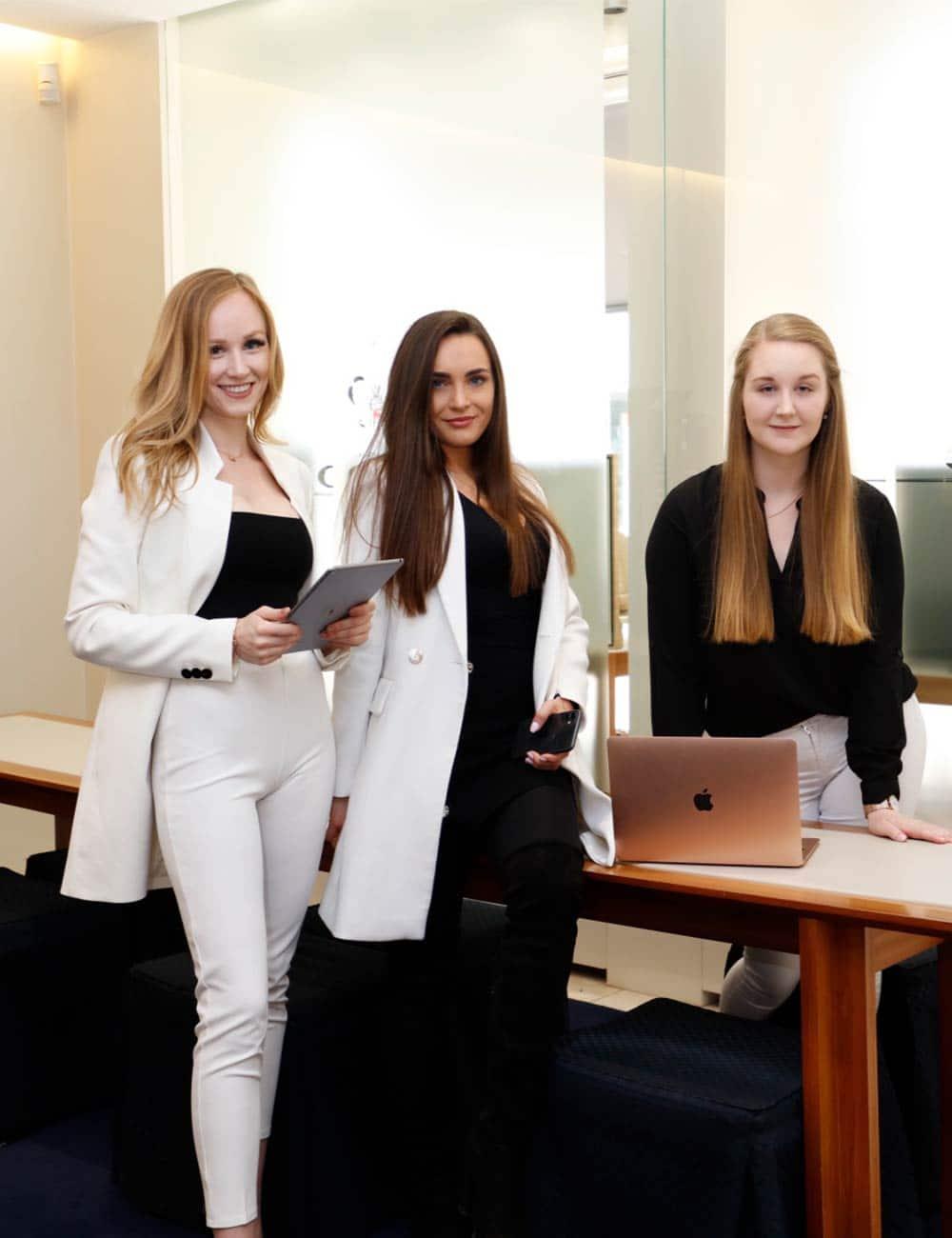 Drei Frauen stehen mit einem Laptop und Tablet im Verkaufsraum des Juwelier Kopp