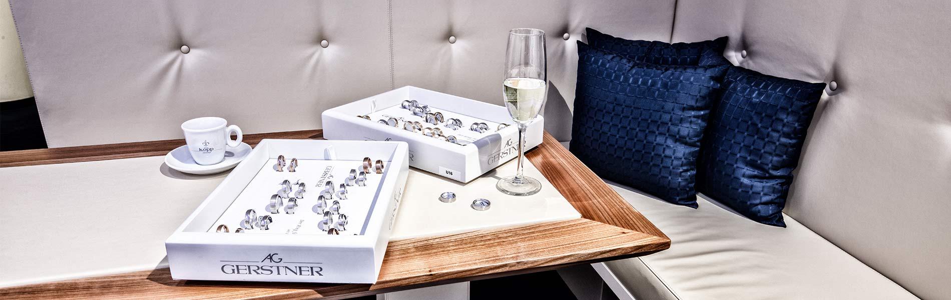 Sitzecke mit blauen Kissen Sektgläsern und Trauringen in der Trauringlounge des Juwelier Kopp
