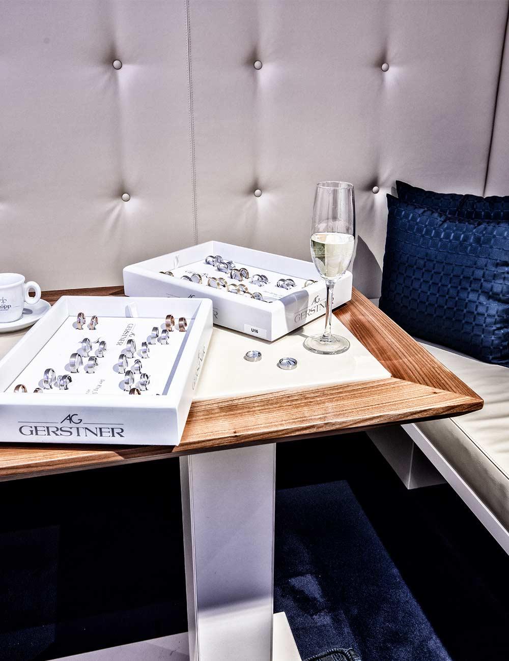 Sitzecke mit blauen Kissen Sektgläsern und Trauringen in der Juwelier Kopp Trauringlounge