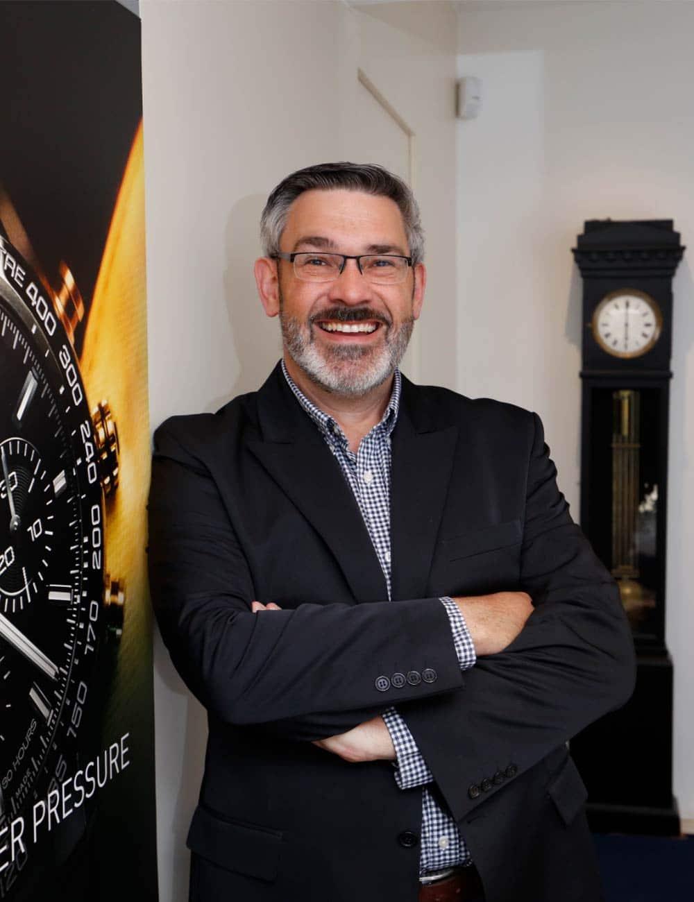 Mann steht im Anzug vor einer schwarzen Standuhr im Juwelier Kopp Heidenheim