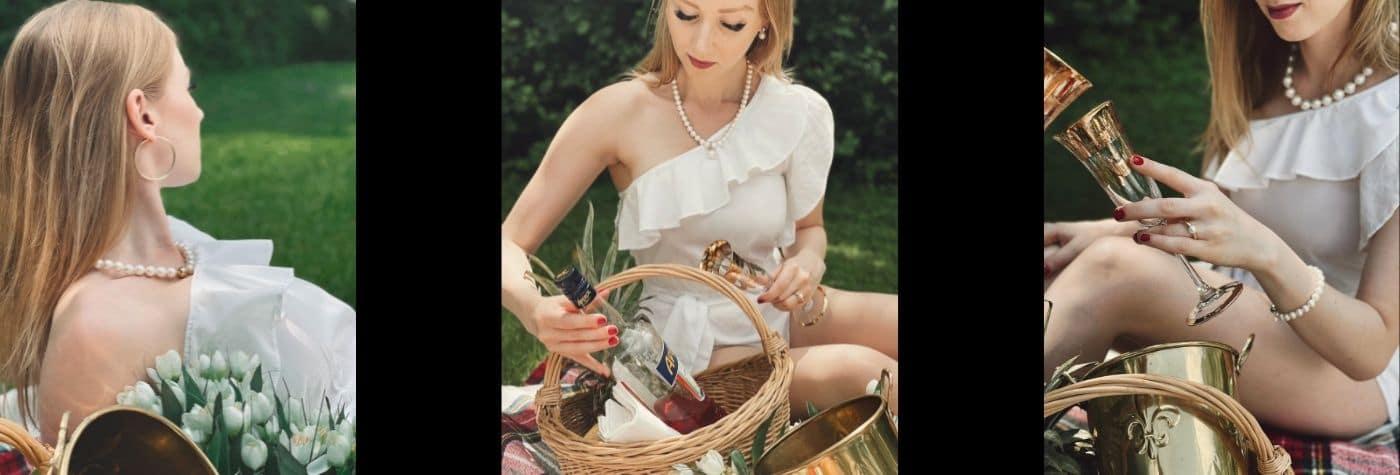 Blonde Frau mit einem Picknickkorb Getränken und Obst trägt Perlenschmuck und ein weißes Kleid