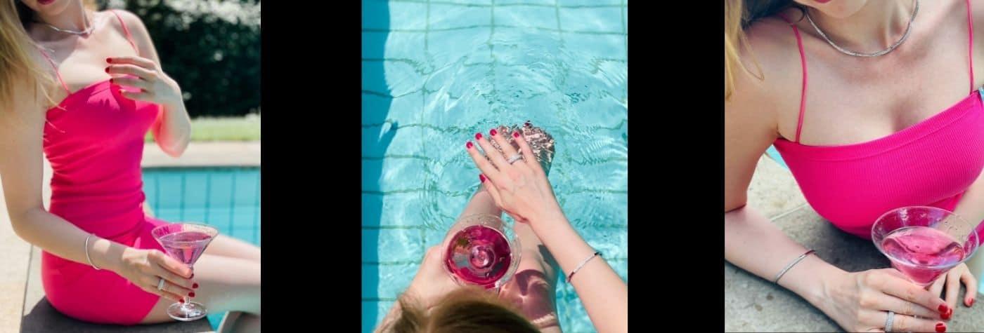 Blonde Frau in pinkem Kleid hält ein pinkes Getränk an einem Pool. Weißgoldfarbener Schmuck von Juwelier Kopp Heidenheim