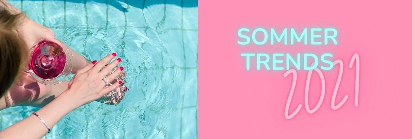 Blonde Frau sitzt mit einem pinken Getränk an einem Pool mit rotem Nagellack und Sommer Schmuck