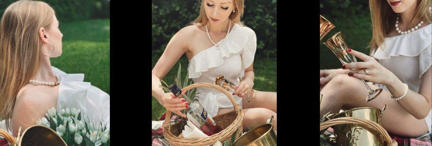 Dame trägt weißes Kleid und Perlenschmuck bei einem Picknick
